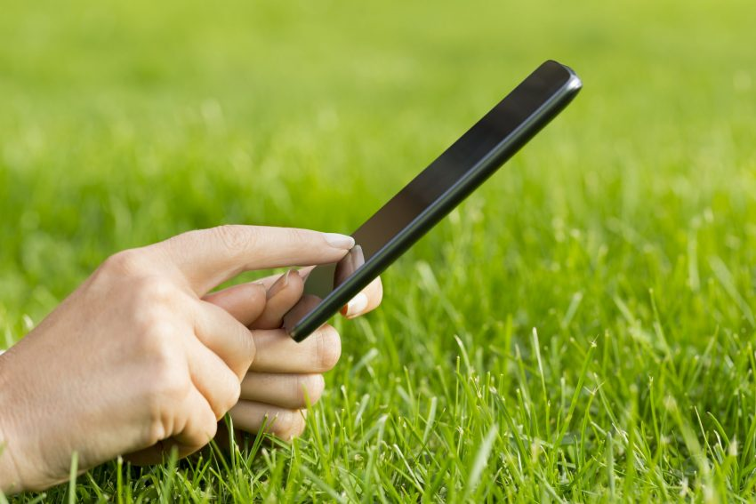 girl on cell phone on green grass