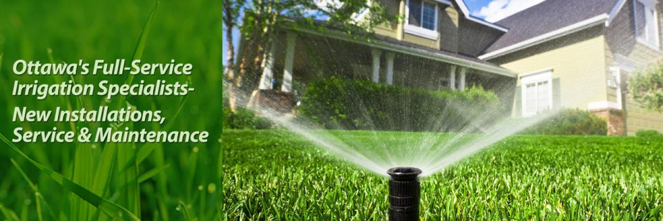 sprinkler watering green grass in front of house